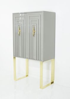 A modern twist on the classic art deco styling. Elegant and symmetrical, the Art Deco Bar Cabinet shows off its style and sophistication through it's trellis doors and its bright gloss greystone finis