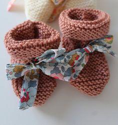 Petits chaussons de laine pour bébé, ornés dun joli lacet en Liberty. Entièrement tricotés à la main, au point mousse, dans une matière douce et confortable. Ils garderont les petits pieds bien au chaud ! Avec le béguin assorti, cest un petit cadeau de naissance qui plaira à coup sûr !