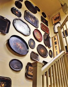 Vintage Tole Trays displayed above the stairs. Striking arrangement.