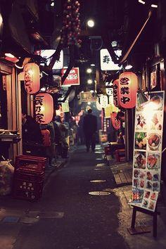 A narrow street in Tokyo with plenty of restaurants