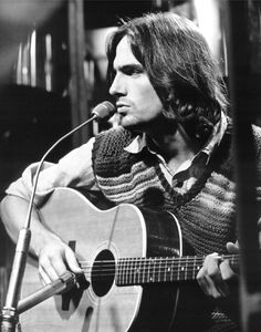 JAMES TAYLOR. Well, the sun is surely sinking down, but the moon is slowly rising.  So this old world must still be spinning around, and I still love you. So close your eyes, you can close your eyes, it's alright. I don't know no love songs, and I can't sing the blues anymore. But I can sing this song...and you can sing this song when I'm gone.