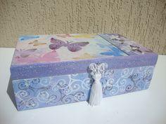 """Caixa em mdf: - Pintura: esponjado e pátina primitiva, detalhes feitos com estêncil e carimbos decorados com chatons (""""strass""""), com um penduricalho na tampa. - Cor: mesclado de azul, rosa, e lilás (interior: marfim respingado com rosa e azul). Feito por Milena Schueda. Disponível em: http://www.elo7.com.br/caixa-decorativa-de-borboletas/dp/4F628A"""