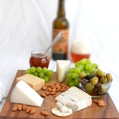 Mediterranean cheese board with olives, grapes, fig jam, almonds, and a barrel-aged ale.