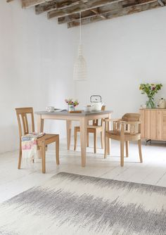 Loaf's concrete-look square Conker kitchen table in this rustic dining room with exposed beams and oak chairs