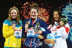 (L-R) Silver medal winner Emily Seebohm, Gold medal winner Missy Franklin of the USA and Bronze medal winner Aya Terakawa of Japan celebrate on the podium after winning the Swimming Women's 100m Backstroke Final on day eleven of the 15th FINA World Championships at Palau Sant Jordi on July 30, 2013 in Barcelona, Spain.