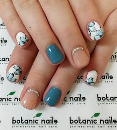 A really pretty nude nail art design with matte green blue polish. You can also see beautiful flower details painted on top of the white polish as well as silver beads aligned at the cuticles of the nude polished nails.