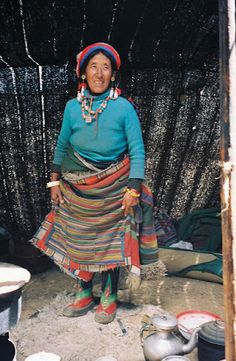 The Tibetan nomad in her yak-hair tent, showing off her footwear.