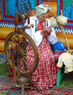 An old woman spinning with a wheel at Kursk Korenskaya Fair