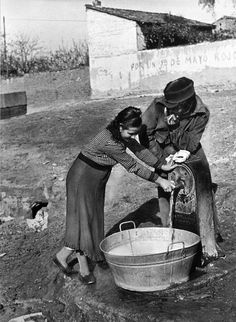 Madrid, Spain. A member of the International Brigades, flirts with a girl from Madrid while she draws water from a well. By Robert Capa, (November-December 1936)