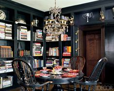 The library in the Kentucky home of fashion designers Mark Badgley and James Mischka has an inviting old-world look, with shelves studded with antlers from European hunting lodges and trophies found at flea markets and on eBay. Antique Windsor chairs surround a table set with Hermès  china and napkins by Leontine Linens. Photographer: Roger Davies  - ELLEDecor.com