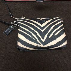 Coach zebra wristlet Used for a short period of time, so convenient to hold when you go out or need to cary small items or even to organize things in your purse! Has wrist strap and zips at the top, only imperfection is slight pink mark on the top corner which is photopgraphed, and the white may not be considered as vibrant as brand new but thats it, has pockets on the inside, open to reasonable offers, no trades Coach Bags Clutches & Wristlets