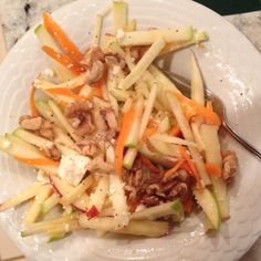 Apple carrot salad with walnuts, feta cheese, lemon, salt, olive oil, pepper, and sugar.