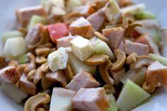 Salade van kipfilet, brie, ijsbergsla, tomaten, komkommer en cashewnoten.