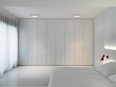 Wardrobe across full wall in an all white bedroom.