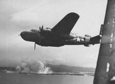 A B-25 supporting the landings at Cape Gloucester as bombs hit Japanese positions prior to the assault.