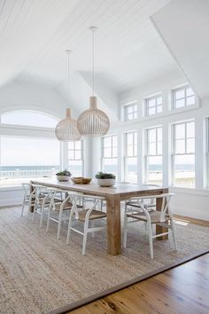 Two modern woven basket light pendants hangs from a white shiplap vaulted ceiling over a long solid wood dining table surrounded by Hans Wegner Wishbone Chairs placed on a gray bound sisal rug.
