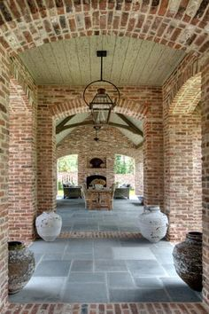 brick breezeway and #outdoor room with #fireplace - love the #brick and the archways