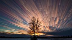 """timestacked"" - Matt Molloy  This does a great job of showing the passage of time through the light sky from the left side of the image into the dark to the right. It also shows the passage of the clouds throughout the day, as well as the sun setting."