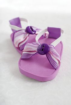 These Purple Stripe sandals are made of craft foam, ribbon, elastic and an accent button. The elastic loop helps the sandals stay on snug and are easy to take on and off.