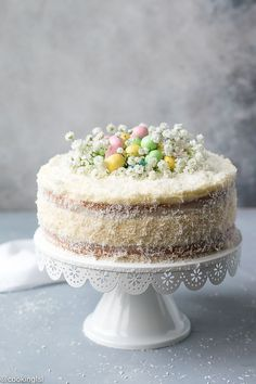 Coconut Cheesecake Cake two layers of sweet coconut cake with cheesecake in the middle, with cream cheese frosting and Easter decorations.