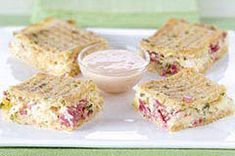 Swiss cheese, sauerkraut and corned beef are layered between crackers in a pan, topped with eggs and milk then baked for puffy Reuben appetizers.