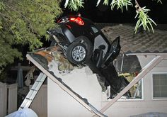 A sport utility vehicle that went airborne sits in the roof of a home in Escondido, Calif., Dec. 11, 2014. Police said a BMW driver lost control during a turn, went off a road and plunged through the garage roof of a home that sits about 20 feet below the roadway. George Strother said the car landed on the hood of his Nissan Pathfinder in the garage and knocked the ceiling down on another car. Neither he nor his wife, or the driver of the car, were hurt. (AP Photo/George Strother)