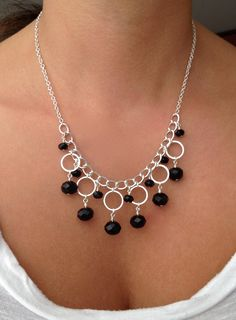 Silver-plated necklace with circle components and black Murano glass beads.