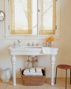 Basic Basket Storage  Since a window over the sink stands in for the typical mirrored medicine cabinet in this Santa Barbara, California, home, a simple woven basket is used to hold towels and other bathroom necessities.