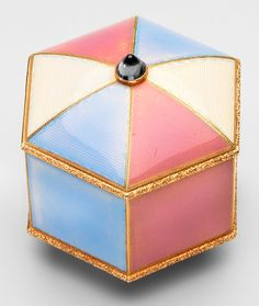 Fabergé (jeweller)   Guilloché enamel, gilt metal, sapphire.  Gift of George V, 1 January 1929. Description:  Hexagonal cream, pale blue and pink guilloché enamel and gold box with convex cover set with cabochon sapphire at centre and base mounted with chased foot rim. Rim and lower edge mounts similarly chased with foliage. Gilt interior.   The Royal Collection.