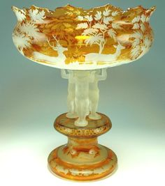 """Monumental sized blown glass pedestal and bowl. 28"""". Amber stained platform and 23"""" wide bowl. Intaglio wheel-cut stag and forest scenes. Three acid cut Lalique type cherubs attach the pedestal to the bowl. They appear to be supporting its massive size. Scalloped cut rim on the bowl. Bohemian, circa 1860"""