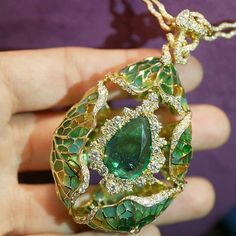 """A vibrant emerald of 7.5 cts is the star of the necklace """" Alibaba & Forty thieves"""" from Masterstrokes by #JewelsEmporium . Hidden in the surrounding cluster and the foliage are 9 diamonds as 9 thieves. 5 larger ones in the cluster, 3 in the center of the side lotus leaves and 1 at the helm of the stelm that links the pendant to the chain.Look for them as the shimmer their existence! With a total of 8.71 cts of brillant-cut diamonds and a surround by lotus leaves enameled on Plique-a-jour…"""