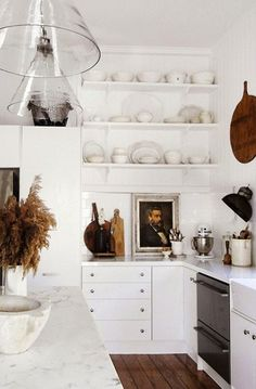 white kitchen with open shelves, marble counter and glass lighting
