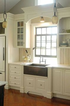 Love the look of this kitchen with those beautiful cabinets and that sink.  To die for.