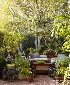 STRIPED FURNITURE ON A BRICK TERRACE The terrace in a Hollywood home has chaise longues with cushions in a Pindler & Pindler fabric, pillows in a Janus et Cie fabric, Moroccan lanterns, and antique English wicker chairs.