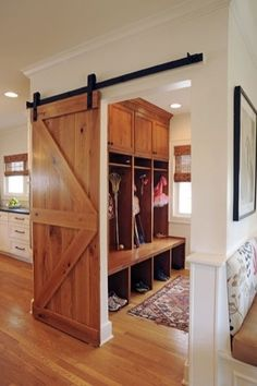 I need this door on every room in my imaginary home --  Maximize space in the mudroom by using a sliding door vs a door that swings inside of the room.  Keeps the clutter concealed and is an interesting architectural feature.  And, a reminder, you can buy the hardware for a barn door at a Feed Supply store.