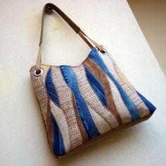 džíska vlnky v písku Větší kabelka je ušitá z béžové rercydžínoviny. Přední strana je kompozicí krásně strukturovaných materiálů v odstínech režné a béžové, doplněnou zajímavě probarvenými kousky modré džínoviny. Stejný motiv v zjednodušené podobě se opakuje i na zadní straně kabelky. Dalším zdobným prvkem je složené ucho z béžového popruhu ...