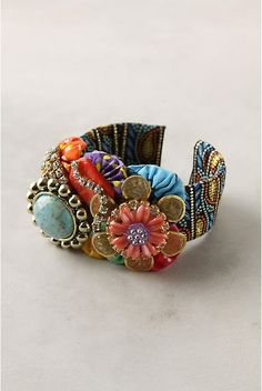 DIY cuff bracelet made from a cuff form, fabric or ribbon, glue, fabric yo-yo's, buttons, earrings or pins & a strand of rhinestone.  Awesome way to use my grandma's old clip-on earrings and broaches