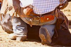 Cowboy holding calf at branding at Chico Basin Ranch. #ChicoBasinRanch