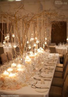 Gold sprayed twigs in tall glass vases with pearl bead garlands  and candles.
