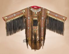 This is an authentic Native American war shirt, handcrafted by American Indian artists. This decorative doe skin leather warrior shirt represents a rich part of Indian history with great attention to