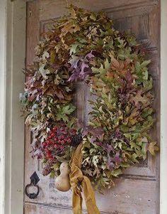 mooie herfst krans van verschillende kleuren blad en rozenbotteltakken.
