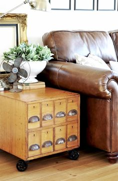 Leather chair, repurposed library card cabinet as side table, black frames, old fan