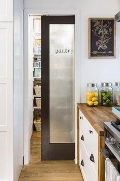 Frosted glass door of pantry in white kitchen