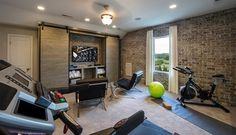 Industrial man cave and exercise room combo features workout equipment and yoga mats placed in front of exposed brick walls.