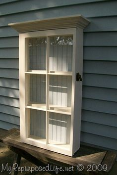 how to make a window cabinet using an old window and a shelf as crown molding. This project was featured at Design Sponge.