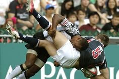 BROUGHT DOWN: Hong Kong's Lee Jones, right, was tackled by Fiji's Osea Kolinisau during their Hong Kong Sevens preliminary rugby game in Hong Kong on Friday. (Bobby Yip/Reuters)