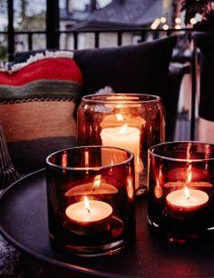 Ein Tablett mit drei Teelichthaltern in gelbbraunem Glas mit brennenden Kerzen.