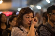 Umbrella Revolution Hong Kong, A woman wipes her eyes as she listens to a speech by a pro-democracy group on a road occupied by protesters in the Admiralty district of Hong Kong on October 9, 2014. Hong Kong has been plunged into the worst political crisis since its 1997 handover as pro-democracy activists take over the streets following China's refusal to grant citizens full universal suffrage. AFP PHOTO / Ed Jones (Photo credit should read ED JONES/AFP/Getty Images)
