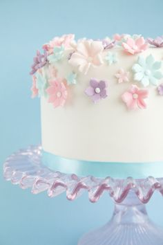 A scattering of medium and small flowers across the tops and over the edge of a cake.