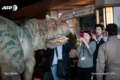A woman takes pictures of Japan's On-Art Corp's 6.4 metre tall dinosaur-shaped mechanical suit dino-tronics robot during a performance at the Sky Lobby of Hikarie building in Tokyo on April 4,...